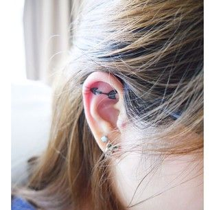 Arrow inner ear tattoo