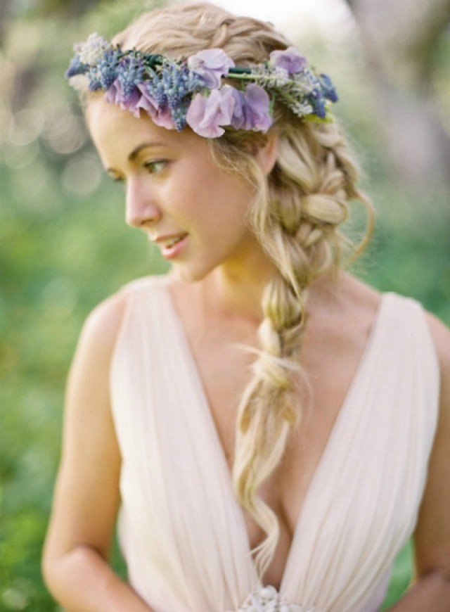 Beautiful braided wedding hairstyle with purple flowers