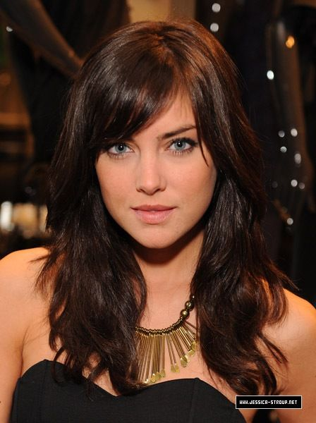 Jessica Stroup with side swept bangs and wavy medium to long hair .