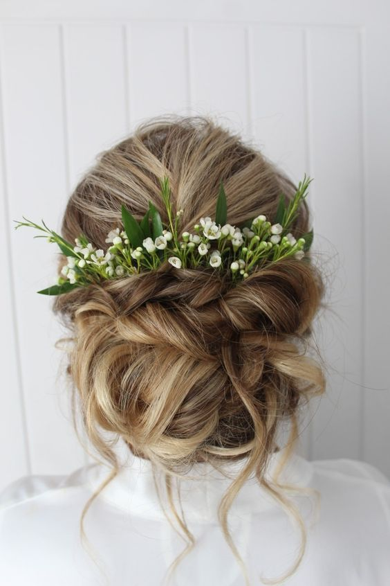 Wedding Hairstyle Updo with greenery and florals as accessories .