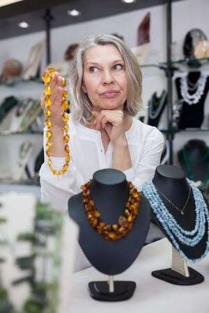 Adult Woman Chooses Jewelry From Turquoise And Amber Jewelery .