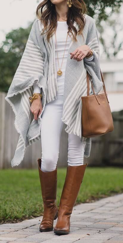 Woman wearing white jeans, white top, gray and white poncho, brown .